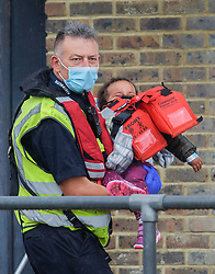 © Licensed to London News Pictures. 10/07/2021. Dover, UK. A child migrant is carried ashore by a Border Force officer at Dover Harbour in Kent after crossing the English Channel. Photo credit: Stuart Brock/LNP