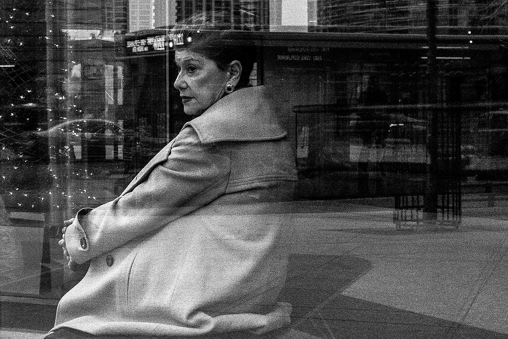 During the holiday season I was waiting outside of a building, when I noticed this lady staring out onto the street. I carefully tried to get the reflections right as cars and vehicles moved in and out of the frame. The lady also was moving her head and eventually gave a long stare. Quickly I made a few exposures, capturing what I feel is a good mix of facial expression and reflections.