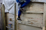 Boy climbs up wall in risk averse playground called The Land on Plas Madoc Estate, Ruabon, Wrexham, Wales.