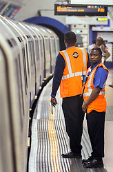 © Licensed to London News Pictures. 07/07/2015. London, UK. London Underground staff observing a one minute silence on the westbound Piccadilly Line platform at Kings Cross Station today, the station which was used by Germaine Lindsay who killed 26 people in the 7th July 2005 bombings in London which killed 52 people in total. Photo credit : James Gourley/LNP