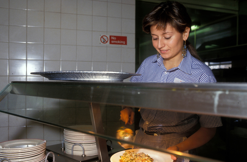 Student working in canteen to supplement her grant UK