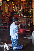 Man reading a pray behind the Golden Statue of Guanyin and Sudhana  from the Jade Buddha Temple interior in Shanghai. Asia, china.