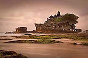 After sunset, Tanah Lot temple gets flooded in soft golden light. This pura was founded in the 16th century and appropriately named Temple of the Land in the Sea.