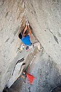 "Kevin Jorgeson climbing the Sierra testpiece steep crack route ""Grand Illusion"" (5.13b/c), at Sugar Loaf, near Lake Tahoe California, while Charlie Barrett belays."