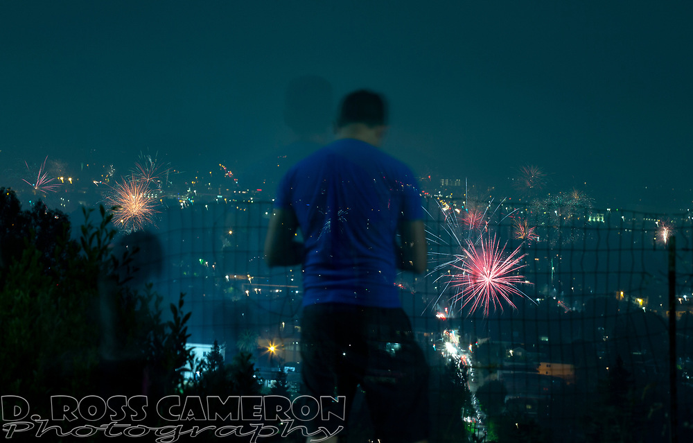 A spectator watches unauthorized fireworks explode over Oakland, Calif., as the United States celebrates the 243rd anniversary of its independence from Great Britain, Thursday, July 4, 2019. (Photo by D. Ross Cameron)