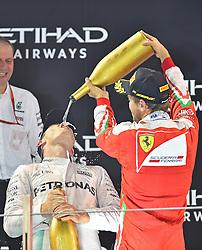 """Sebastian Vettel (GER#5), Scuderia Ferrari """"duscht"""" Weltmeister 2016, 2. Platz im Rennen, Nico Rosberg (GER#6), Mercedes AMG Petronas Formula One Team mit Rosenwasser beim Rennen im Rahmen des Grand Prix von Abu Dhabi auf dem Yas Marina Circuit / 271116<br /> <br /> ***Abu Dhabi Formula One Grand Prix on November 27th, 2016 in Abu Dhabi, United Arab Emirates - Race Day ***"""
