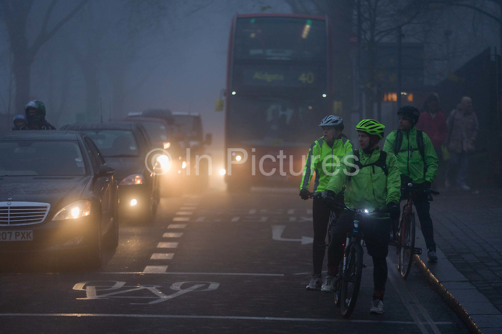 Commuting cyclists wait to cross a junction at dawn on a foggy morning in south London. Wearing high-visibility jackets and flashing strobe lights on their handlebars, as recommended by safety campaigners and the police, they can be seen by motorists during rush-hour. It is dawn at around 8.45 on this winter morning, a dark and miserable time of day in this south London suburb from where Londoners start their journeys north into the City. Cars and a bus wait for the lights to change, their headlights shining in the fast-dispersing fog on Denmark Hill. His shadow crosses the road's surface as he pedals over the junction.