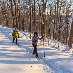 Two women snowshoeing through the forest above Indian Hill Reservoir in West Newbury, Massachusetts.