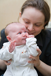 Young mother holding her new five week old baby,