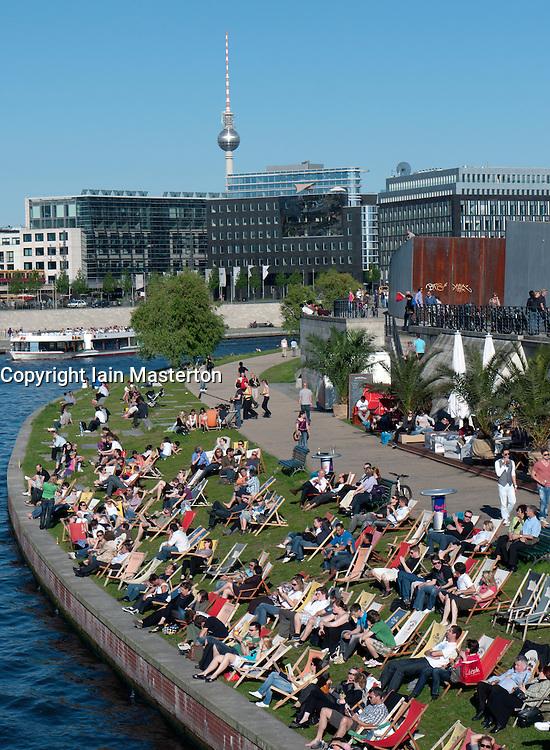 Busy waterside cafe in summer  beside Spree River in central Mitte Berlin Germany