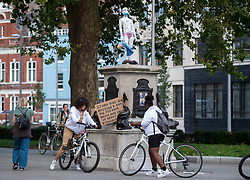 "© Licensed to London News Pictures; 19/09/2020; Bristol, UK. People view and photograph a new statue and placards against child exploitation and child sex trafficking which have been placed on the plinth from where the statue of slave trader Edward Colston was pulled down and thrown into Bristol docks on 07 June during an All Black Lives/Black Lives Matter protest in memory of George Floyd, a black man who was killed on May 25, 2020 in Minneapolis in the US by a white police officer, that made headlines around the world. The artist behind this new statue against child exploitation is not known. Since the Colston statue was pulled down various other statues and artworks have been placed on the empty plinth without permission from Bristol City council, including a statue ""A Surge of Power (Jen Reid) 2020"" by sculptor Marc Quinn of protester Jen Reid who was at the previous protest on 07 June. Photo credit: Simon Chapman/LNP."