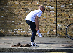 © Licensed to London News Pictures. 24/06/2021. London, UK. A member of the public takes off his shoes to wade through water in St John's Wood, North London, where a burst pipe has has cause flooding across a number of streets in the area. Photo credit: Ben Cawthra/LNP