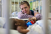 Tracey, a councilor from BigShoes Durban, spending time with 5 year old Kwanele who is lying in his hospital bed.  In Clairwood hospital. Durban, South Africa.   The boy is an inpatient in the hospital where Bigshoes Foundation provides pediatric palliative and hospice care.  Kwanele sadly passed away 2 days after this photo was taken.