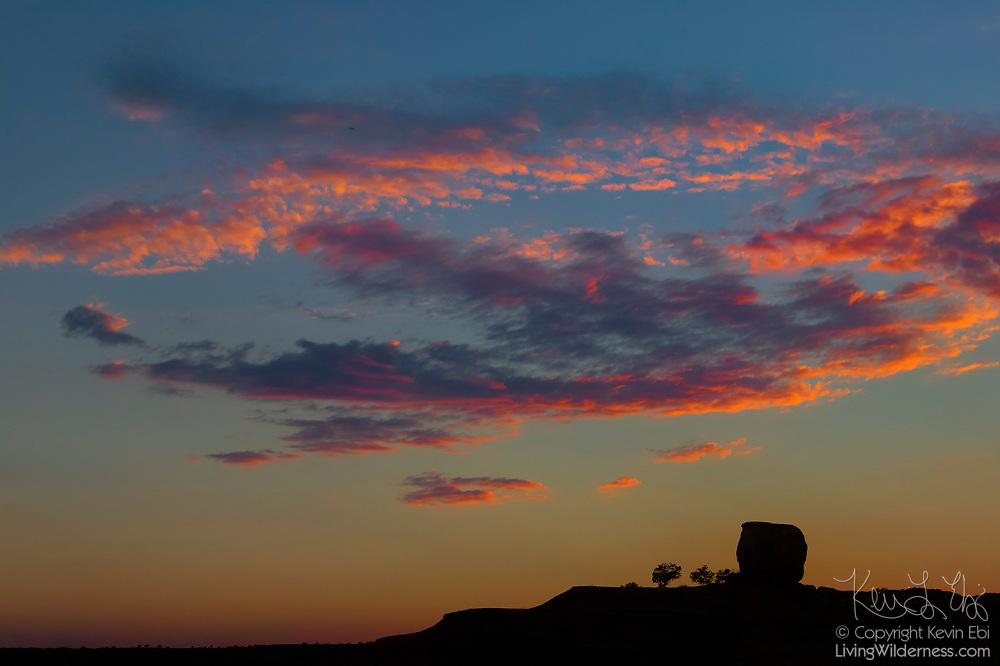 A layer of altocumulus clouds are turned fiery red by the setting sun as a large rock formation appears to observe in Capitol Reef National Park, Utah.