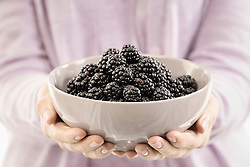 Mid section view of woman holding a bowl of blackberry, Bavaria, Germany