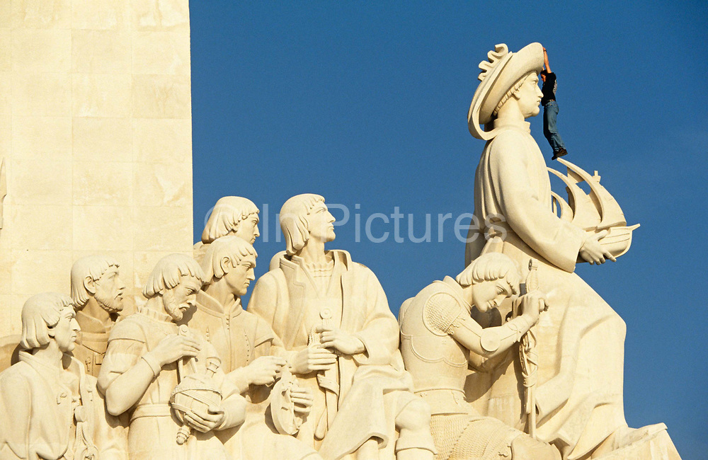 A man hangs from the hat of Prince Henry, Duke of Viseu, at the Monument of the Discoveries at Belem, Lisbon. The man has found a way to scale part of the 177 foot (54 metre) high celebration to Henry, otherwise known as Henry the Navigator, or Seafarer. The trespasser is dwarfed by the giant, oversized effigies and the man hangs by his fingers and rests his foot on Henry's ship's sail which points out to sea. It is a clear day with blue skies and the slightly yellow stone is side-lit to show each feature of the carvings in fine detail. It is a classic scene of Portguese history depicted during the 1960s fascist Portuguese President Salazar's regime. Henry remains one of ocean-conquering Portugal's most famous of cartographers, whose explorers discovered new routes around Africa and the Atlantic. Although he was called Prince Henry the Navigator by the English, Prince Henry never actually sailed on any of the voyages of discovery he sponsored. Instead, Prince Henry established a school for the study of the arts of navigation, mapmaking, and shipbuilding. This would allow sailors to better guide their ships and to come up with new ship designs. Immediately behind Henry is King Manuel I then poet Luis de Camōes. The eight figures are carved by sculptor Leopoldo Almeida and along with the monument, were commissioned for the 1960 world exhibition to commemorate the 500th anniversary of Henry's death in 1460.
