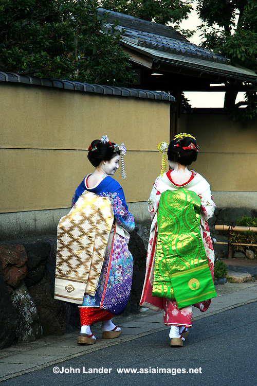 """Geisha on the streets of Arashiyama Kyoto - geiko as they are called in Kyoto are traditional, female Japanese entertainers whose skills include performing various Japanese arts such as classical music and dance. Apprentice geisha are called maiko literally """"dance child"""". It is the maiko, with her white make-up and elaborate kimono and hairstyle, that has become the stereotype of a geisha to Westerners."""