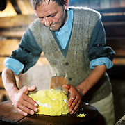A shepherd makes mamaliga whilst smoking a cigarette at a sheepfold in Lunca Ilvei, Romania. Shepherds live on 'urda' a kind of cottage cheese made from whey together with mamaliga or maize mush, made by cooking maize flour with water in a cauldron until it can be turned out into a board as a solid block and sliced like bread.
