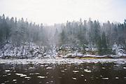 Lite snowfall and broken pieces of ice floating in River Gauja with sandstone cliffs and forest in back, near Sigulda, Gauja National Park (Gaujas Nacionālais parks), Latvia Ⓒ Davis Ulands | davisulands.com