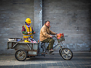 Man carrying work material on a tricycle in central Beijing, China