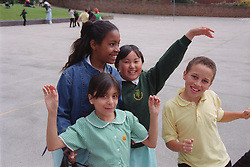 Multiracial group of primary school children playing together in school playground,