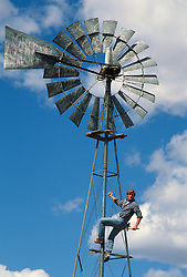 Man Climbing up a windmill in New Mexico