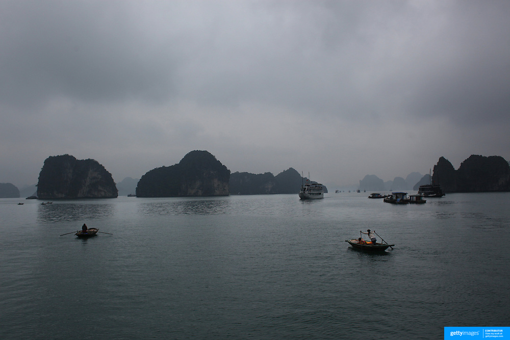 Local sellers row to tourist boats to sell their goods in Ha Long Bay, Vietnam. The bay consists of a dense cluster of 1,969 limestone monolithic islands. Ha Long Bay, is a UNESCO World Heritage Site, and a popular tourist destination. Ha Long, Bay, Vietnam. 11th March 2012. Photo Tim Clayton