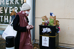 © Licensed to London News Pictures. 08/11/2020. London, UK. A woman wearing a face covering walks past an overflowing bin. Restaurants are currently only providing take away services due to the second coronavirus lockdown, which is resulting in bins overflowing outside shops in Haringey Arena Shopping Park, north London. The lockdown will last until Wednesday 2 December, to control the increase of coronavirus cases. Photo credit: Dinendra Haria/LNP