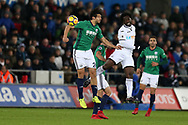 Wilfried Bony of Swansea city is challenged in the air by Ahmed Hegazi of West Brom (26).  Premier league match, Swansea city v West Bromwich Albion at the Liberty Stadium in Swansea, South Wales on Saturday 9th December 2017.<br /> pic by  Andrew Orchard, Andrew Orchard sports photography.