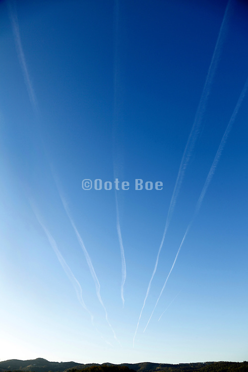 various airplane vapor trails converging towards one point at the horizon