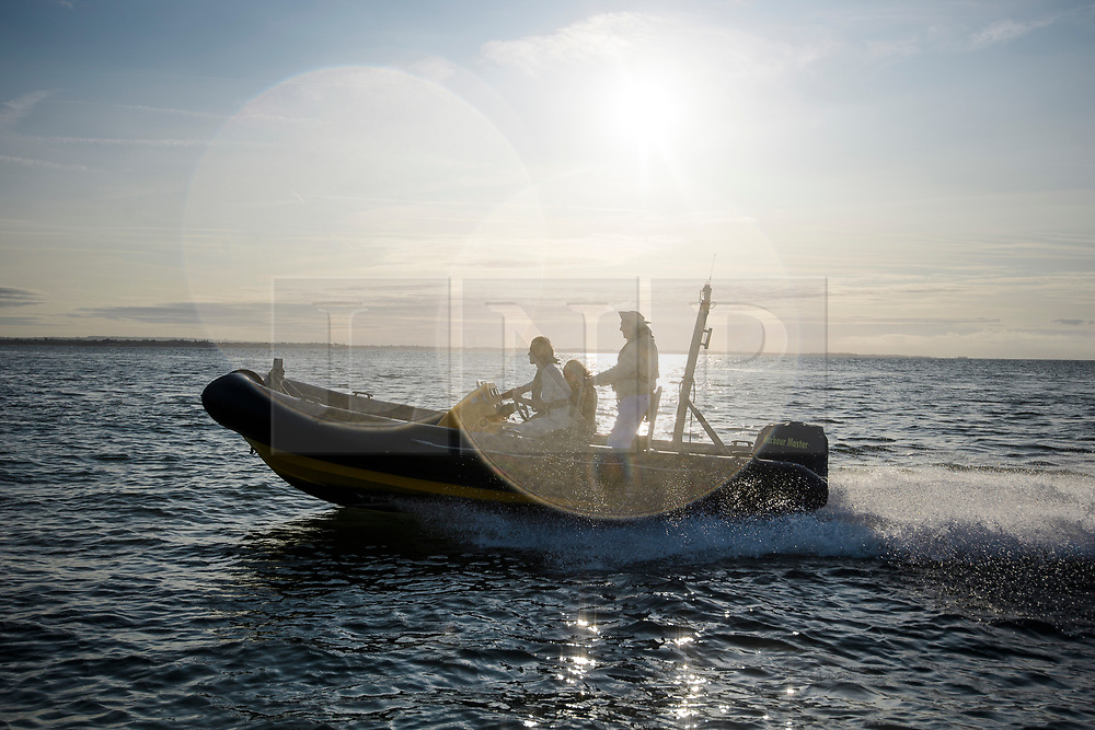 © Licensed to London News Pictures. 24/08/2017. Solent, UK. Two players make their way to the island at sunrise. Teams take part in the Brambles Bank Cricket Match in the middle of The Solent strait on August 24, 2017. The annual cricket match between the Royal Southern Yacht Club and The Island Sailing Club, takes place on a sandbank which appears for 30 minutes at lowest tide. The game lasts until the tide returns. Photo credit: Ben Cawthra/LNP