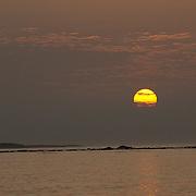 Large yellow sun setting over the Galapagos islands. Galapagos, Ecuador.