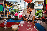 "19 AUGUST 2014 - BANGKOK, THAILAND:  A member of the Lehigh Leng Kaitoung Opera troupe paints the signboard announcing the name of the opera being performed at Chaomae Thapthim Shrine, a small Chinese shrine in a working class neighborhood of Bangkok. The performance was for Ghost Month. Chinese opera was once very popular in Thailand, where it is called ""Ngiew."" It is usually performed in the Teochew language. Millions of Chinese emigrated to Thailand (then Siam) in the 18th and 19th centuries and brought their culture with them. Recently the popularity of ngiew has faded as people turn to performances of opera on DVD or movies. There are still as many 30 Chinese opera troupes left in Bangkok and its environs. They are especially busy during Chinese New Year and Chinese holiday when they travel from Chinese temple to Chinese temple performing on stages they put up in streets near the temple, sometimes sleeping on hammocks they sling under their stage. Most of the Chinese operas from Bangkok travel to Malaysia for Ghost Month, leaving just a few to perform in Bangkok.        PHOTO BY JACK KURTZ"