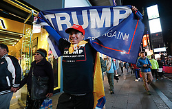 © Licensed to London News Pictures. 09/11/2016. New York City, USA. A man waves a pro Donald Trump flag above his head while walking through Times Square, New York City, on Wednesday, 9 November. Photo credit: Tolga Akmen/LNP