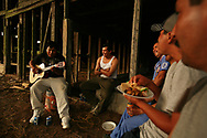 Jose Yanes Cristobal plays guitar as Juan Percastre, center, and his uncle, Antonio Yanes,  right, all of Hidalgo, Mexico, join co-workers in eating, drinking, and listening to music during a celebratory dinner.