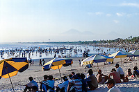 Bali, Badung, Kuta. Come dusk the local population and tourists gather on the beach to look at the sunset or to take a walk. This was a clear day with the mountains to the north clearly visible.