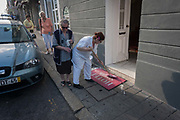 As others try to squeeze through a space on the narrow pavement, a hotel employee cleans the matt in front of the Hotel do Norte, on 20th July, in Porto, Portugal. Scrubbing the step and the matt which contain the name of this establishment, the cleaner takes up most of the space on the sidewalk.