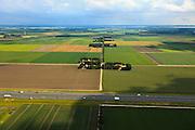 Nederland, Noordoostpolder, 30-06-2011; Johannes Postweg (doorsneden door de A6), Nagele rechts aan de horizon. De Noordoostpolder (NOP), is een voorbeeld van moderne grootschalige polder met rationele verkaveling. De aanleg van de polder maakte  deel uit van de Zuiderzeewerken (plan Lely) en viel in 1942 droog. De meeste boerderijen (en dorpen) zijn van na de tweede wereldoorlog..The northeast polder (NOP), is an example of modern large-scale polder with rational allotment. The construction of the polder was part of the Zuiderzee Works (Lely plan), in 1942 the polder was dry. Most of the building, farmhouses and villages, is post-war..luchtfoto (toeslag), aerial photo (additional fee required).copyright foto/photo Siebe Swart