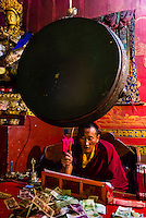 Buddhist monk drumming, Tsurphu Monastery, Gurum, Doilungdeqen County, Tibet (Xizang, China).