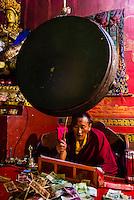Buddhist monk drumming, Tsurphu Monastery, Gurum, Doilungdeqen County, Tibet (Xizang, China).