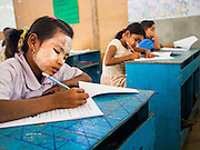 04 MARCH 2014 - MAE SOT, TAK, THAILAND: Students take their final exams at the Sky Blue School in Mae Sot. There are approximately 140 students in the Sky Blue School, north of Mae Sot. The school is next to the main landfill for Mae Sot and serves the children of the people who work in the landfill. The school relies on grants and donations from Non Governmental Organizations (NGOs). Reforms in Myanmar have alllowed NGOs to operate in Myanmar, as a result many NGOs are shifting resources to operations in Myanmar, leaving Burmese migrants and refugees in Thailand vulnerable. The Sky Blue School was not able to pay its teachers for three months during the current school year because money promised by a NGO wasn't delivered when the NGO started to support schools in Burma. The school got an emergency grant from the Burma Migrant Teachers' Association and has since been able to pay the teachers.    PHOTO BY JACK KURTZ