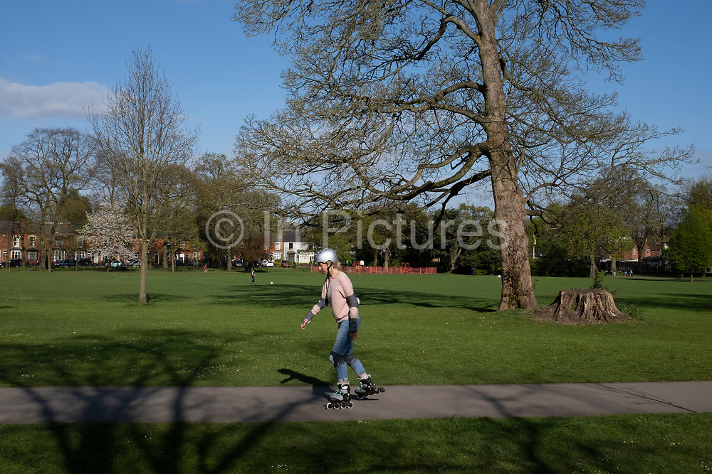 Local response to Coronavirus is felt on a street by street level with some rollerblading exercise in Kings Heath Park on 13th April 2020 in Birmingham, England, United Kingdom. Coronavirus or Covid-19 is a new respiratory illness that has not previously been seen in humans. While much or Europe has been placed into lockdown, the UK government has put in place more stringent rules as part of their long term strategy, and in particular social distancing.
