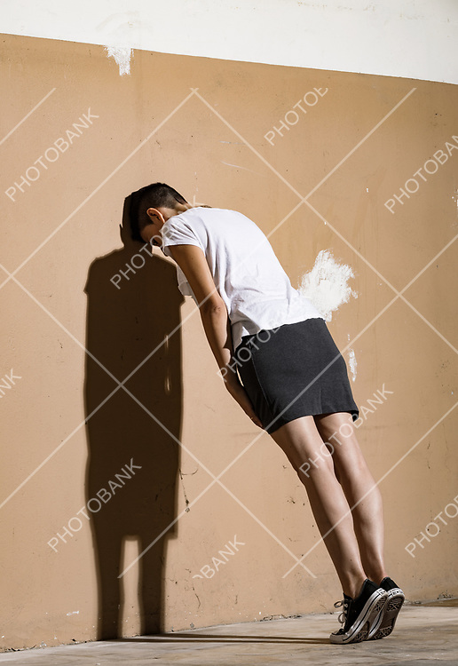 A young woman push the wall and there is a big shadow about the body.