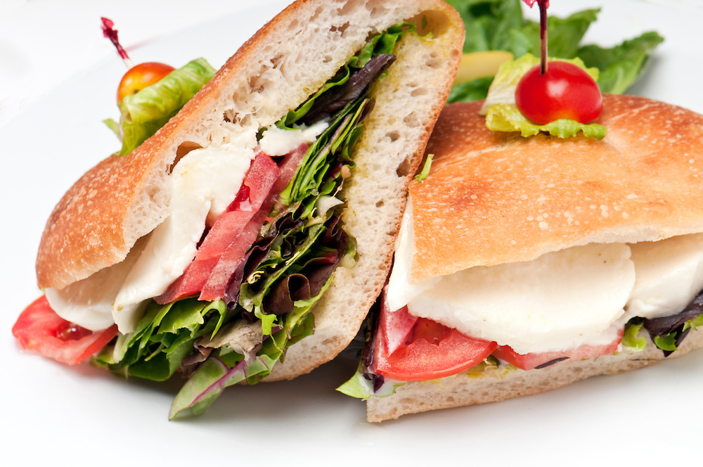 Close up of sandwich of mozzarella, lettuce and tomato.