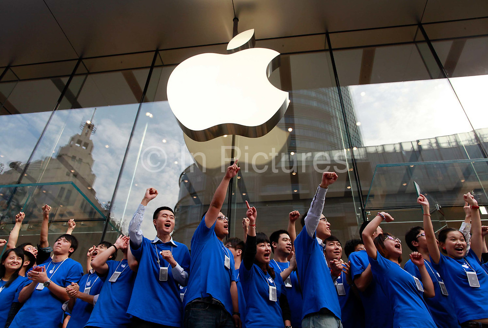 Apple Inc. employees pump their fists in the air as they open the company's new store in Shanghai, China, on Friday, Sept. 23, 2011. Apple Inc. is currently has 5 stores in mainland China as it struggles to open enough stores to stave off competition of its popular iPhones and iPads