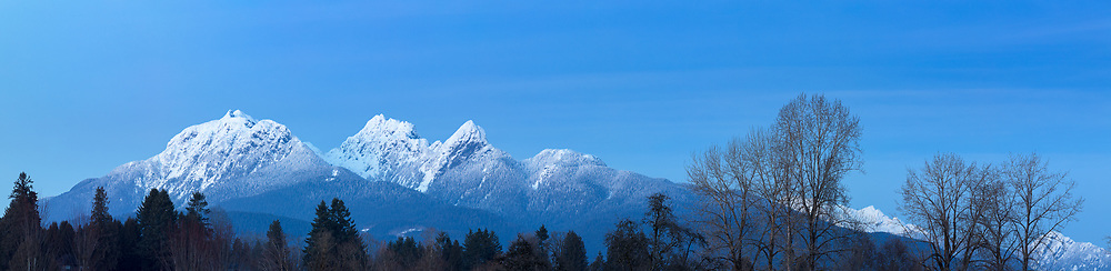 Blue hour panorama of the Golden Ears (Mount Blanshard) as photographed from Derby Reach Regional Park at Meunch Bar in Langley, British Columbia, Canada.