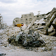 A crushed car in down-town Port Au Prince, steel wreckage from this school is  a typical part of the visual language in Port Au Prince now . On Tuesday 12th of January at 16.53pm local time the biggest Earthquake to hit Haiti for 200 years struck with devastating force. 230,000 people were killed, 300,000 injured and 1.2 million left needing emergency shelter. Survivors have lost family, homes, livelihoods and essential services. Hospitals, schools and government buildings were also destroyed'. These pictures are of the survivors three weeks later.