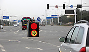 SHIJIAZHUANG, CHINA - OCTOBER 26: (CHINA OUT)<br /> <br /> Two Men in a boxed Traffic Light  Direct Traffic <br /> <br /> Two men stand in a box painted as the traffic light to direct traffic on the road on October 26, 2015 in Shijiazhuang, Hebei Province of China. As the traffic light hadn't worked for a long time at a crossing, two men who worked in a nearby company stood in a box which was painted red lights on two opposite sides and green lights on other two opposite sides to direct traffic voluntarily on the road. Relevant departments started to solve the problem of the broken traffic light, and the traffic police would guide the cars on rush hours. <br /> ©Exclusivepix Media