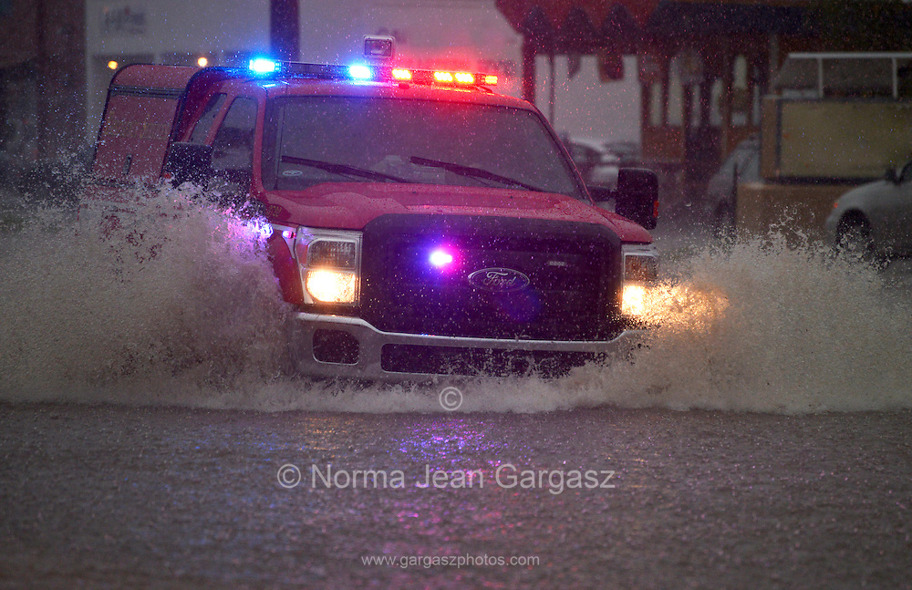 An emergency services vehicle drives through flooded streets during a monsoon storm, Sonoran Desert, Tucson, Arizona, USA.