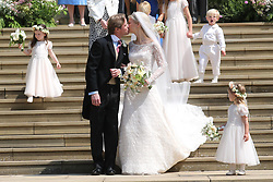 Newlyweds Thomas Kingston and Lady Gabriella Windsor share a kiss on the steps of the chapel after their wedding at St George's Chapel in Windsor Castle.